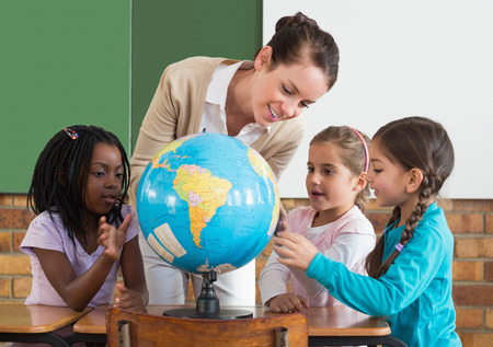 Foto de Cute pupils and teacher in classroom with globe at the elementary school - Imagen libre de derechos
