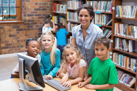 Photo for Cute pupils and teacher looking at computer in library at the elementary school - Royalty Free Image