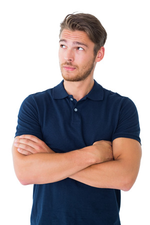 Foto de Handsome young man thinking with arms crossed on white background - Imagen libre de derechos