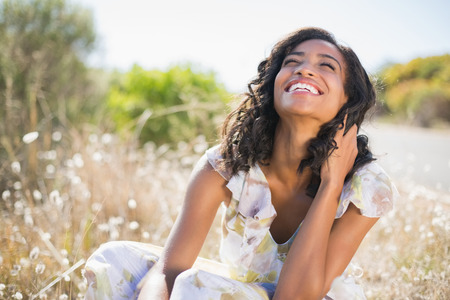 Photo pour Happy pretty woman sitting on the grass in floral dress on a sunny day in the countryside - image libre de droit