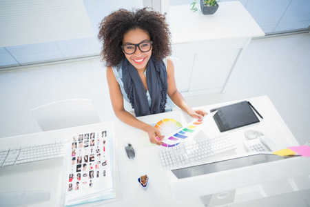 Photo pour Pretty designer working at her desk in her office - image libre de droit