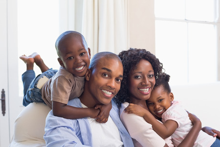 Photo pour Happy family posing on the couch together at home in the living room - image libre de droit