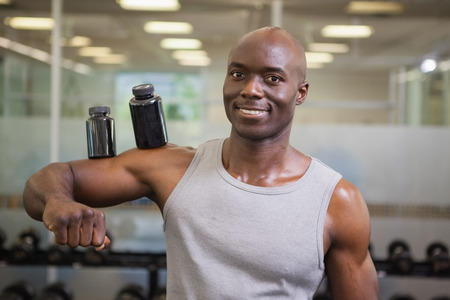 Portrait of male body builder holding bottles with supplements on his biceps