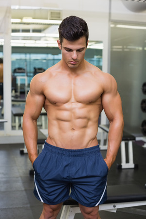 Photo for Shirtless muscular man looking down in gym - Royalty Free Image