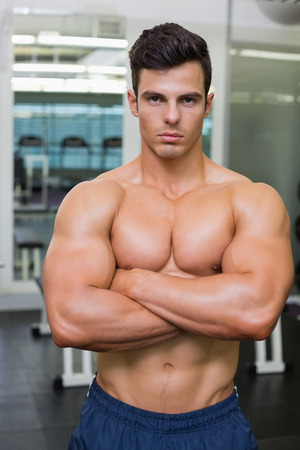 Photo for Serious shirtless young muscular man standing in gym - Royalty Free Image