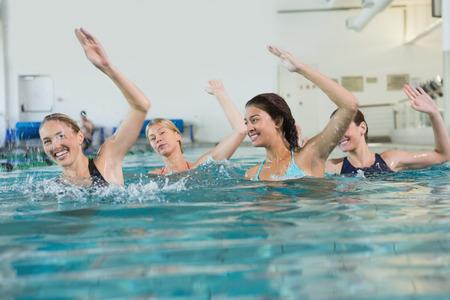 Foto de Female fitness class doing aqua aerobics in swimming pool at the leisure centre - Imagen libre de derechos