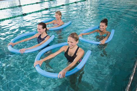 Foto de Fitness class doing aqua aerobics with foam rollers in swimming pool at the leisure centre - Imagen libre de derechos