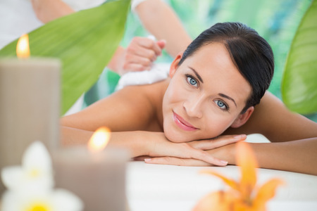 Foto de Beautiful brunette enjoying a herbal compress massage at a luxury spa - Imagen libre de derechos