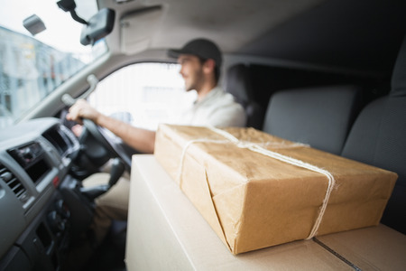 Foto de Delivery driver driving van with parcels on seat outside the warehouse - Imagen libre de derechos
