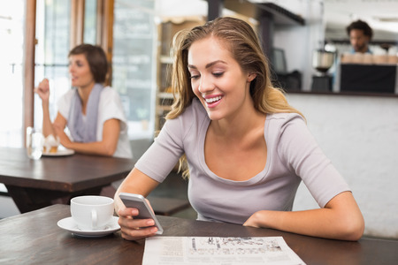 Photo for Pretty blonde sending text message at the coffee shop - Royalty Free Image