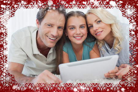 Composite image of portrait of a girl and her parents using a tablet against snow