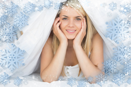 Smiling relaxed young woman lying in bed against snow