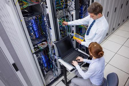 Foto de Team of technicians using digital cable analyser on servers in large data center - Imagen libre de derechos