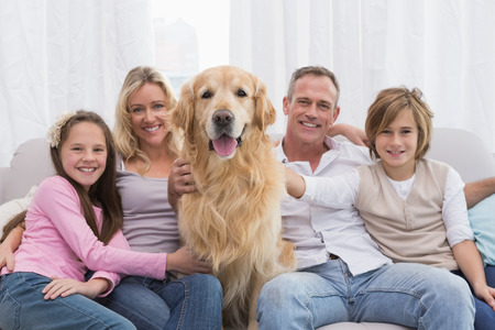 Photo pour Cute family relaxing together on the couch with their dog at home in the living room - image libre de droit