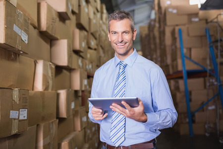 Photo pour Portrait of male manager using digital tablet in warehouse - image libre de droit
