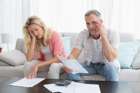 Worried couple calculating bills on the couch at home in the living room