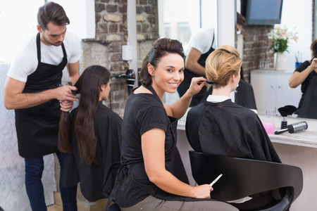 Photo pour Hairdressers working on their clients at the hair salon - image libre de droit