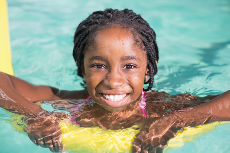 Foto de Cute little girl swimming in the pool at the leisure center - Imagen libre de derechos