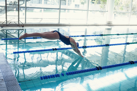 Photo pour Side view of a fit swimmer diving into the pool at leisure center - image libre de droit