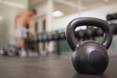 Foto de Focus on large black kettlebell in weights room at the gym - Imagen libre de derechos