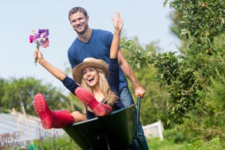 Photo pour Man pushing his girlfriend in a wheelbarrow at home in the garden - image libre de droit