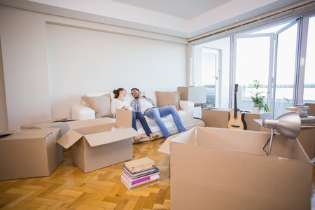 Foto per Cute couple taking a break from unpacking in their new home - Immagine Royalty Free