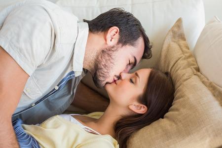 Foto de Cute couple kissing on couch at home in the living room - Imagen libre de derechos