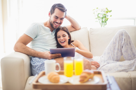 Photo for Cute couple relaxing on couch with tablet at breakfast at home in the living room - Royalty Free Image