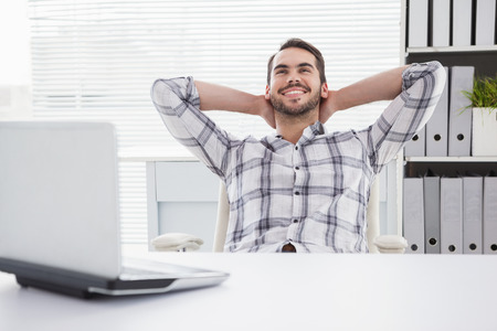 Photo pour Casual businessman relaxing at desk leaning back in his office - image libre de droit