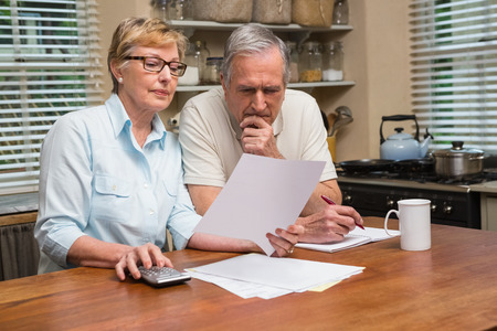 Foto de Senior couple working out their bills at home in the kitchen - Imagen libre de derechos