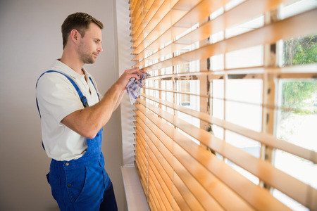 Photo pour Handyman cleaning blinds with a towel in a new house - image libre de droit