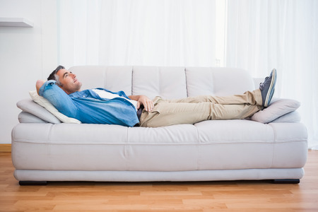 Photo pour Smiling man lying and relaxing on the couch at home in the living room - image libre de droit