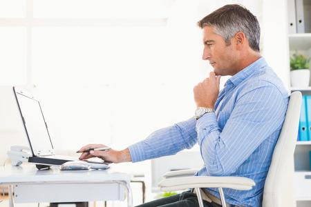 Foto de Man in shirt using laptop and thinking in his office - Imagen libre de derechos