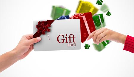 Foto de Hands holding card against gift card with festive bow - Imagen libre de derechos