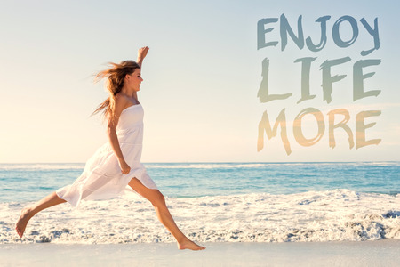 Photo pour Beautiful blonde in white sundress jumping up on the beach against enjoy life more - image libre de droit