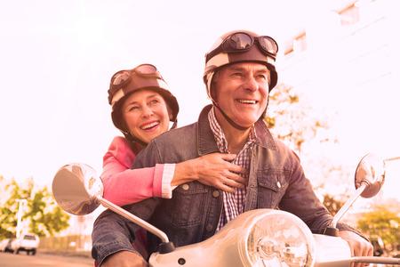 Foto de Happy senior couple riding a moped on a sunny day - Imagen libre de derechos