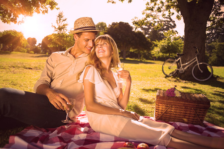 Photo pour Cute couple drinking white wine on a picnic smiling at each other on a sunny day - image libre de droit