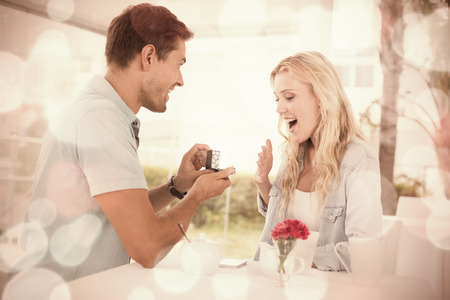 Man proposing marriage to his shocked blonde girlfriend on the cafe terrace on sunny day