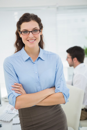 Photo for Smiling businesswoman with arms crossed in the office - Royalty Free Image