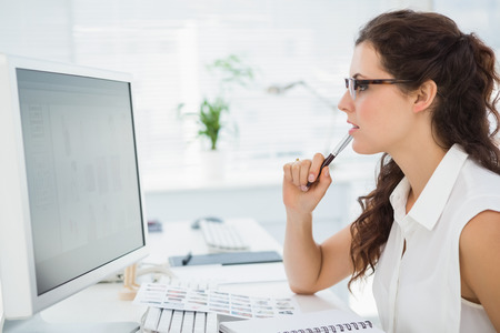 Photo for Focused businesswoman with glasses using computer in the office - Royalty Free Image
