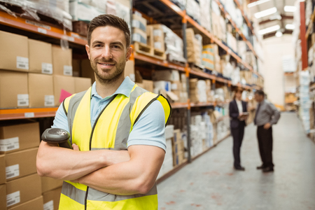 Photo for Smiling worker standing with arms crossed in a large warehouse - Royalty Free Image