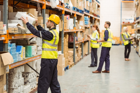 Photo for Warehouse worker taking package in the shelf in a large warehouse in a large warehouse - Royalty Free Image
