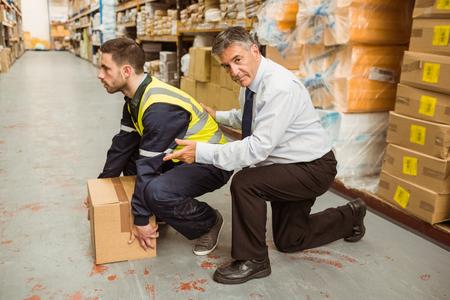 Foto de Manager training worker for health and safety measure in a large warehouse - Imagen libre de derechos