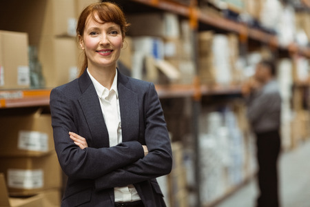 Foto de Female manager with arms crossed in a large warehouse - Imagen libre de derechos