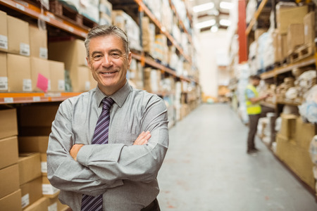 Photo pour Smiling businessman with crossed arms in a large warehouse - image libre de droit