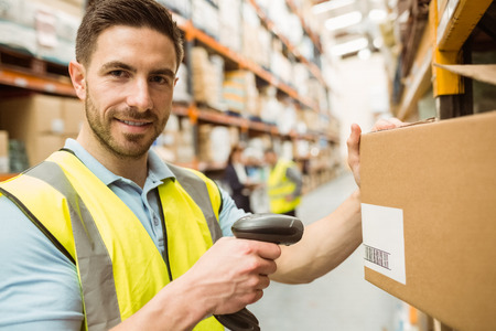 Photo for Warehouse worker scanning box while smiling at camera in a large warehouse - Royalty Free Image