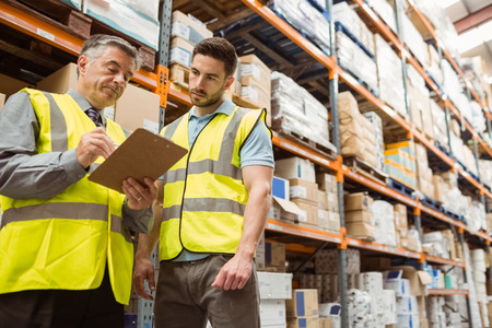 Photo pour Warehouse manager speaking with foreman in a large warehouse - image libre de droit