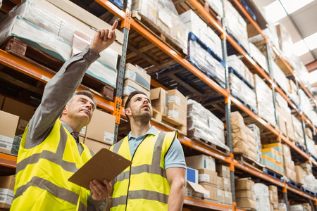 Photo pour Warehouse manager and foreman working together in a large warehouse - image libre de droit