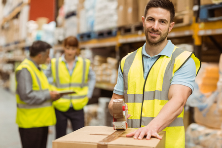 Photo for Smiling warehouse workers preparing a shipment in a large warehouse - Royalty Free Image