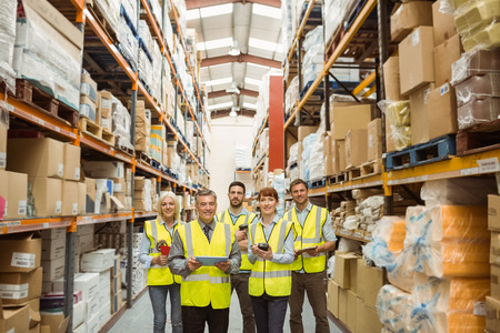 Photo pour Smiling warehouse team looking at camera in a large warehouse - image libre de droit